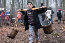 A Syrian refugee child carries buckets used in the making of maple syrup in Mississauga, Canada [Getty]
