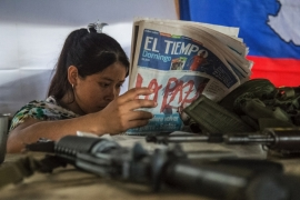 Yoli, reads El Tiempo: Uribe wants to go back to war, says Santos. The word 'Peace' is splashed across the front page in bold red letters [Tomas Ayuso/Al Jazeera]