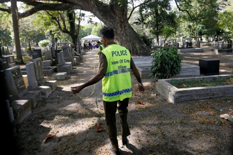 A police officer prepares to take part in the exhumation of Wickrematunge's body [Dinuka Liyanawatte/Reuters]