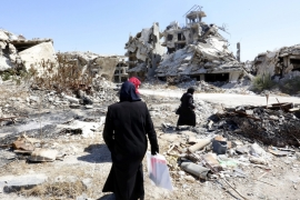People walk between rubble in the city of Homs in Syria [EPA]