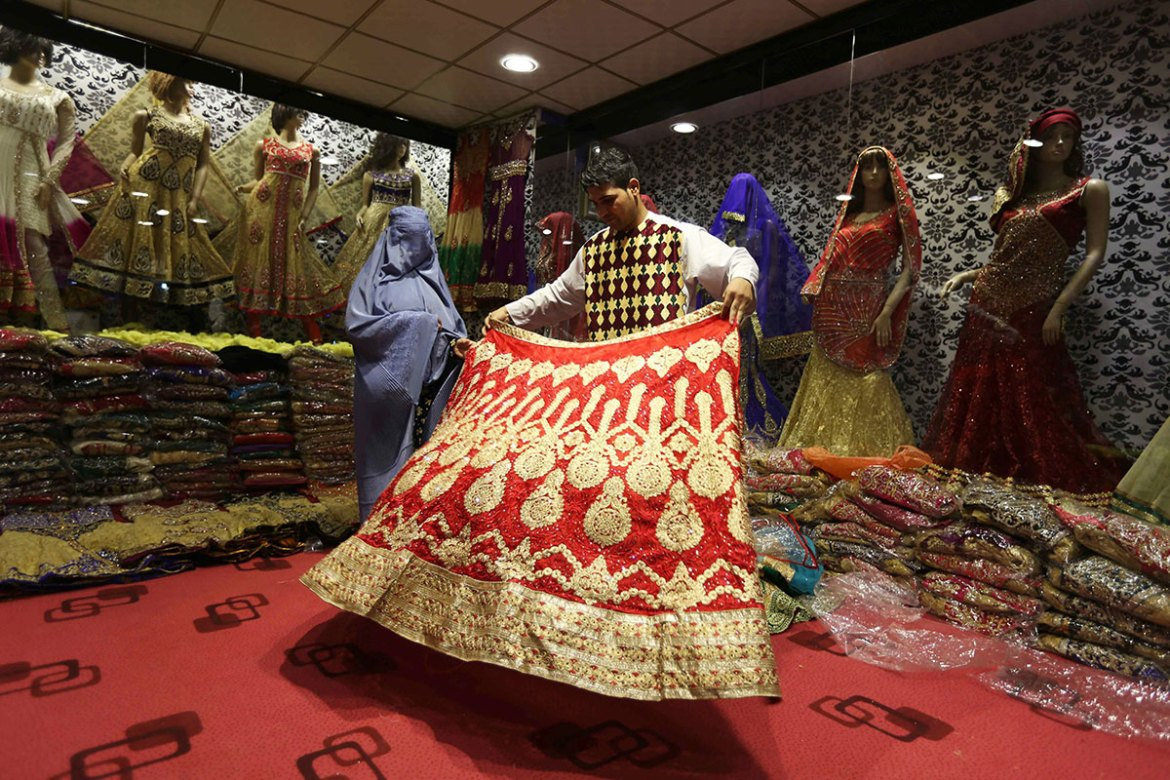 An Afghan checks out dresses on the festive occasion l in Herat, Afghanistan. Eid al-Adha is the holiest of the two Muslims holidays celebrated each year. It marks the yearly Muslim pilgrimage (Hajj) to visit Mecca, the holiest place in Islam. [Jalil Rezayee/EPA]