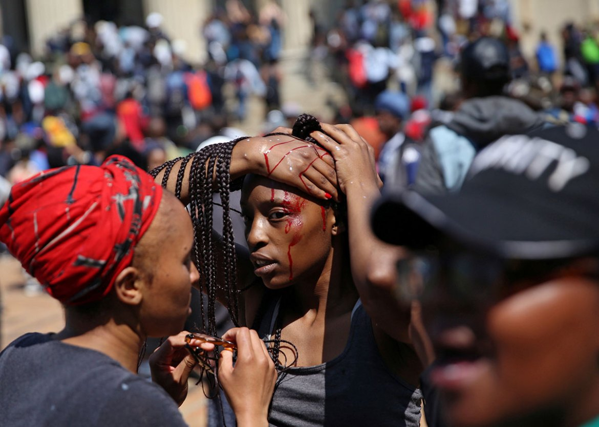 An injured student is attended to by her schoolmates after clashes with security at University of the Witwatersrand on Tuesday, as countrywide protests entered a third week [Siphiwe Sibeko /Reuters]
