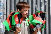 An Afghan boy sells the national flag on a roadside in Jalalabad, Afghanistan [EPA]