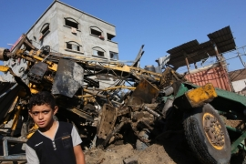 A Palestinian boy looks at the damage following an Israeli air strike on a workshop in Gaza city [EPA]