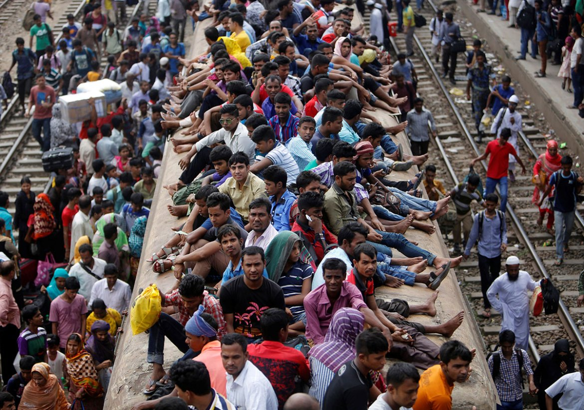 People travelling home to celebrate Eid sit atop a commuter train in Dhaka, Bangladesh. [Mohammad Ponir Hossain/Reuters]