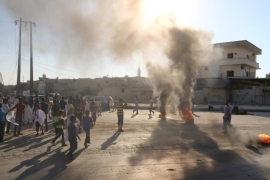 People gather near burning tyres during a demonstration against forces loyal to Assad and calling for aid to reach Aleppo [REUTERS]