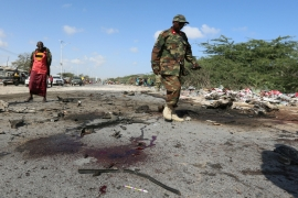 A soldier inspects the scene of the explosion where a general and his bodyguards were killed [Feisal Omar/Reuters]