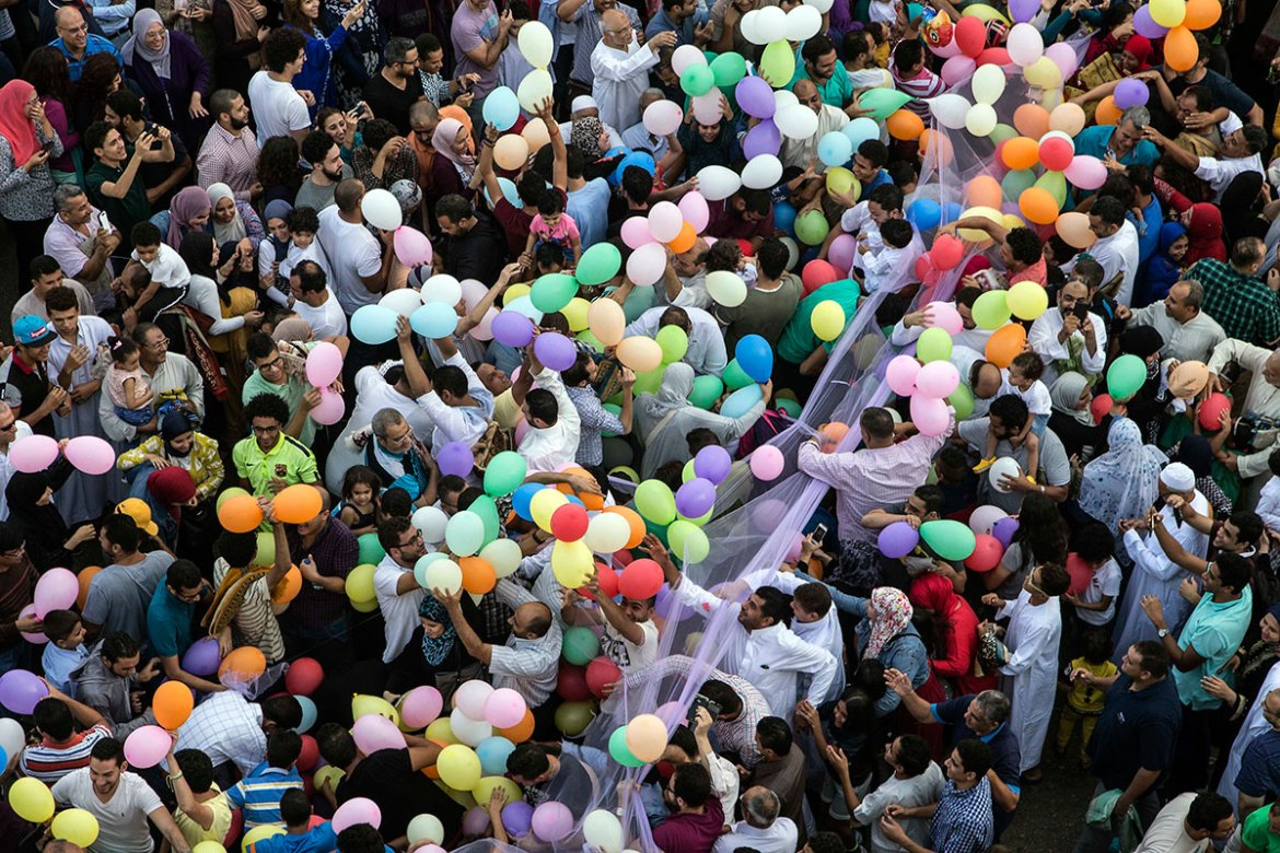 Egyptians try to catch balloons distributed for free after Eid prayers outside Al-Seddik Mosque in Cairo, Egypt. [Roger Anis/AP]