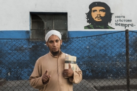 In Havana, Mohammed Dawud, 28, a Cuban convert, stands in front of a mural of Che Guevara [Carlo Bevilacqua/Parallelozero]