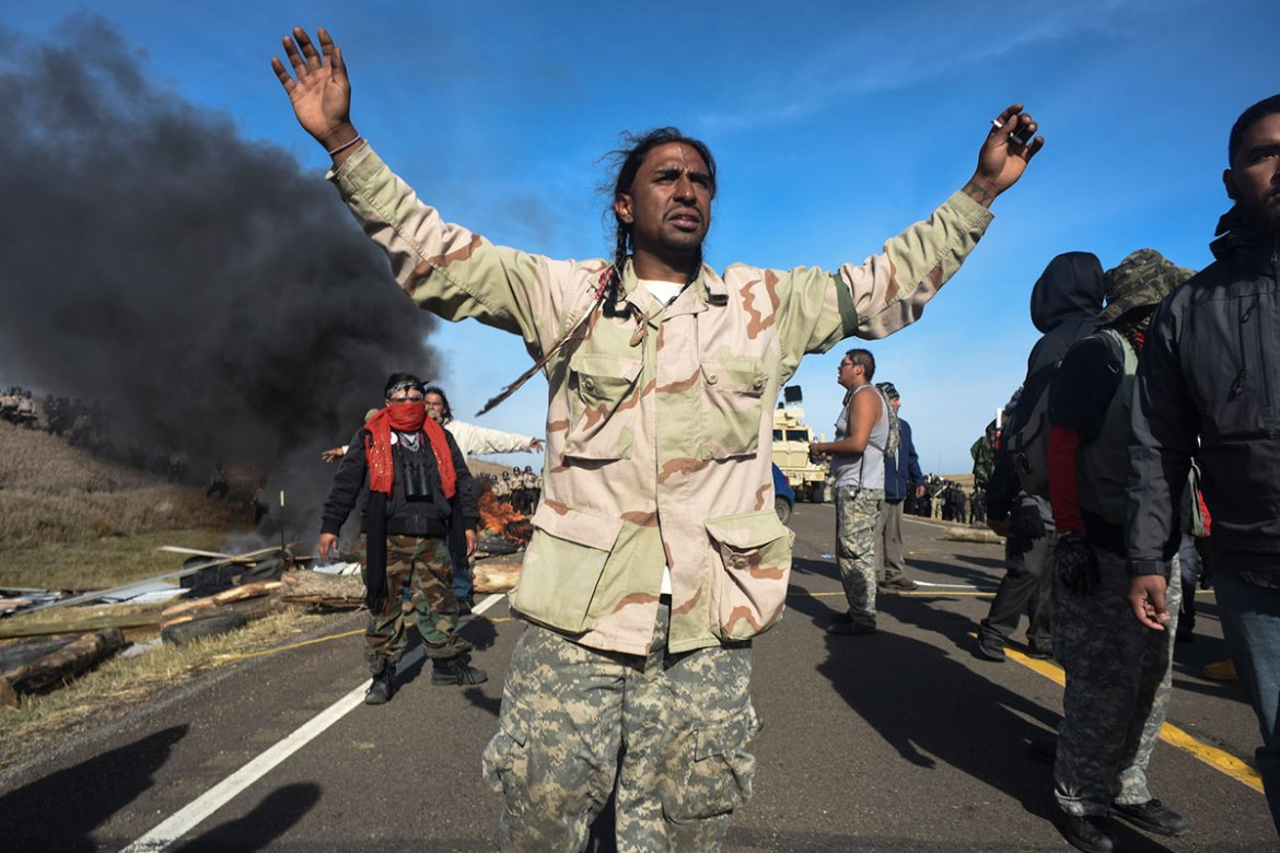 A protester calls on his colleagues to step back as over 100 heavily armed police push towards their protest camp. [Jason Patinkin/Al Jazeera]