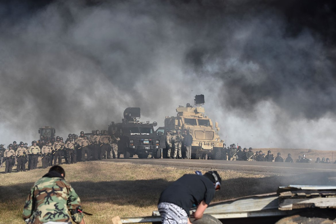 Heavily armed police march on a camp where Native Americans prevented construction of an oil pipeline. [Jason Patinkin/Al Jazeera]
