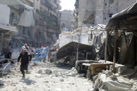 A civil defence member runs at a market hit by air strikes in Aleppo's rebel-held al-Fardous district, Syria [Reuters]