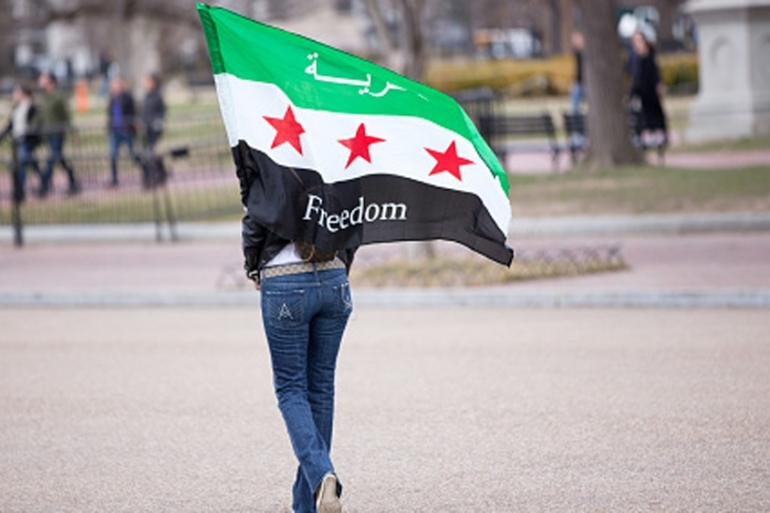 A woman carries a Syrian freedom flag in a park across the street from the White House in Washington DC [Getty]