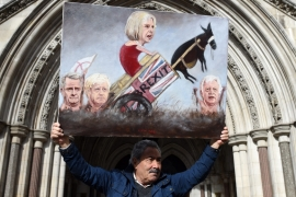 Political artist Kaya Mar poses with a painting depicting the new British Prime Minister, Theresa May, and key Brexit ministers outside the Royal Courts of Justice in London [EPA]
