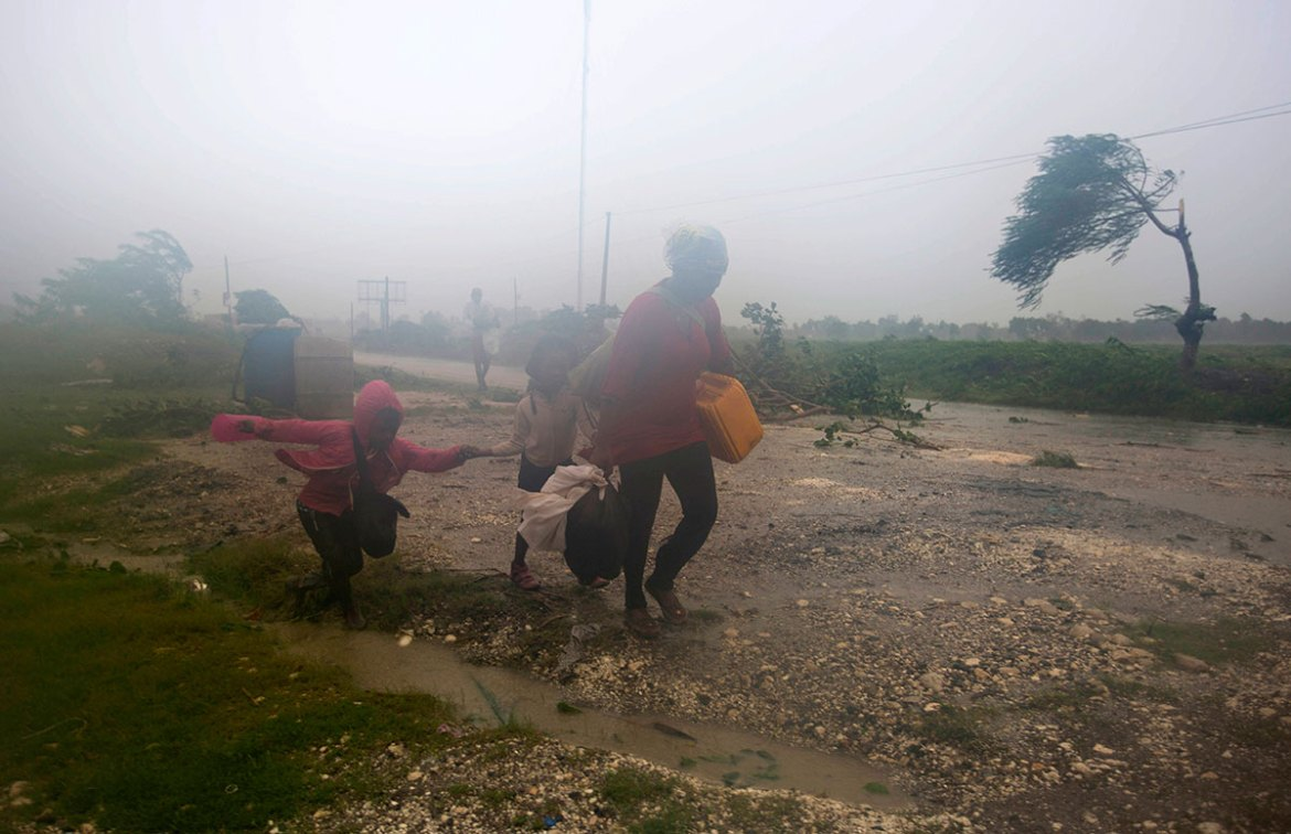 Residents head to a shelter in Leogane, Haiti. Hurricane Matthew slammed into Haiti's southwestern tip howling with 230kph winds on Tuesday, tearing off roofs in the poor and largely rural area, uprooting trees and leaving rivers bloated and choked with debris. [Dieu Nalio Chery/AP]