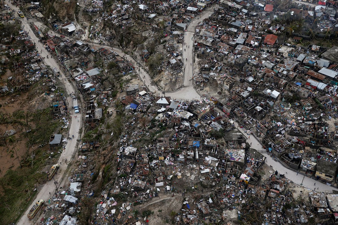 People walk down the streets next to destroyed houses in Jeremie, Haiti. [Carlos Garcia Rawlins/Reuters]