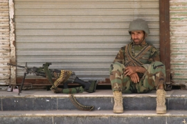 An Afghan National Army soldier sits in front of a closed shop in Kunduz, Afghanistan [REUTERS]