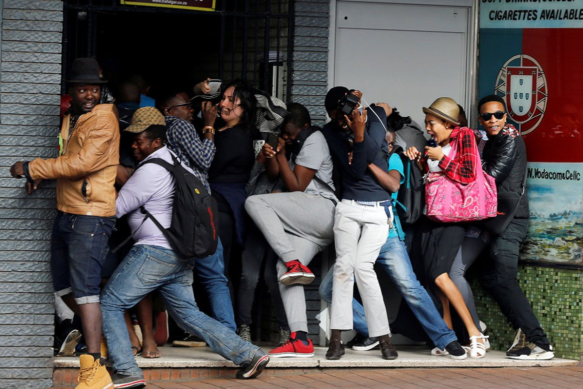 Students demanding free education react as they are fired on by riot police officers during a protest outside the University of the Witwatersrand at Braamfontein, in Johannesburg, South Africa. [Siphiwe Sibeko/Reuters]