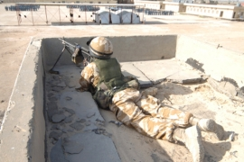 A British soldier provides security from a rooftop in Basra, Iraq [Getty]