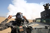 Iraqi forces wear gas masks for protection, as smoke billows in the background from al-Mishraq chemical plant [AFP]