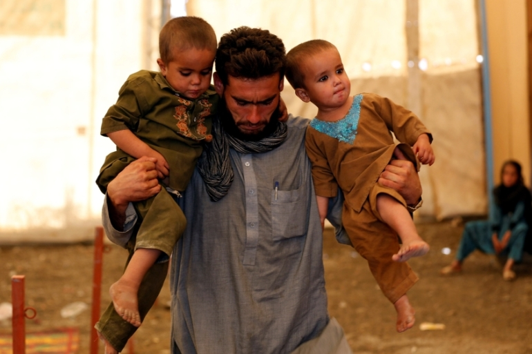 An Afghan man holds his children after arriving at a UNHCR registration centre in Kabul, Afghanistan [REUTERS]