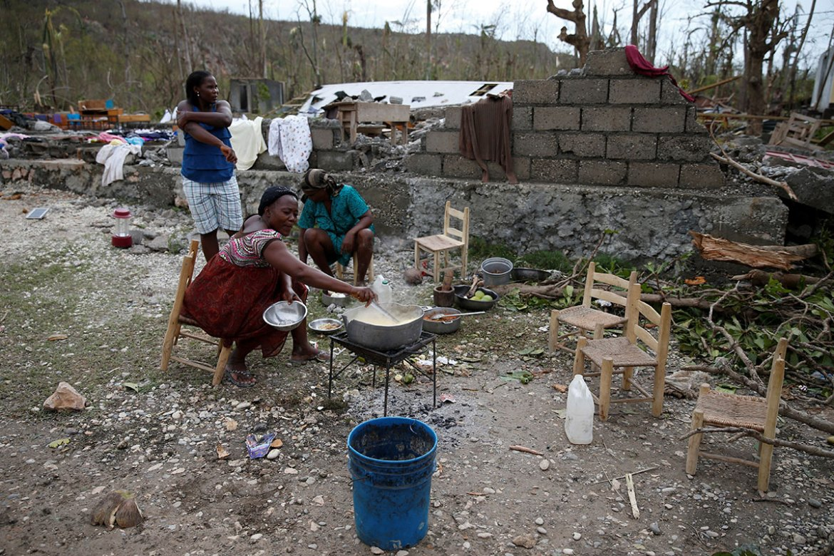 Women cook their meals in a partially destroyed school used as a shelter in Jeremie, in the Grand'Anse department of `Haiti. [Carlos Garcia Rawlins /Reuters]