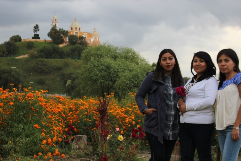Activists from protest group Cholula: Viva y Digna [Alive and Dignified] with the Great Pyramid of Cholula [Ryan Mallett-Outtrim/Al Jazeera]