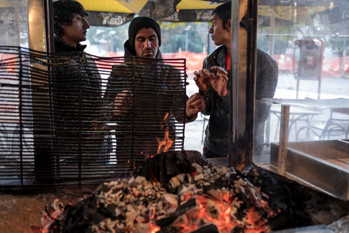 Refugees get warm at a kiosk in 'Afghan Park'. Most, about 70-80 percent of the refugees in Serbia are from Afghanistan. [Ioana Moldovan/Al Jazeera]