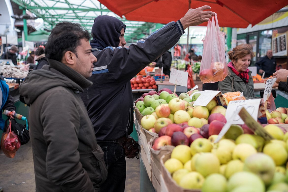 Refugees buy fruit in a market in the vicinity of the refugee aid centre, Miksaliste. [Ioana Moldovan/Al Jazeera]