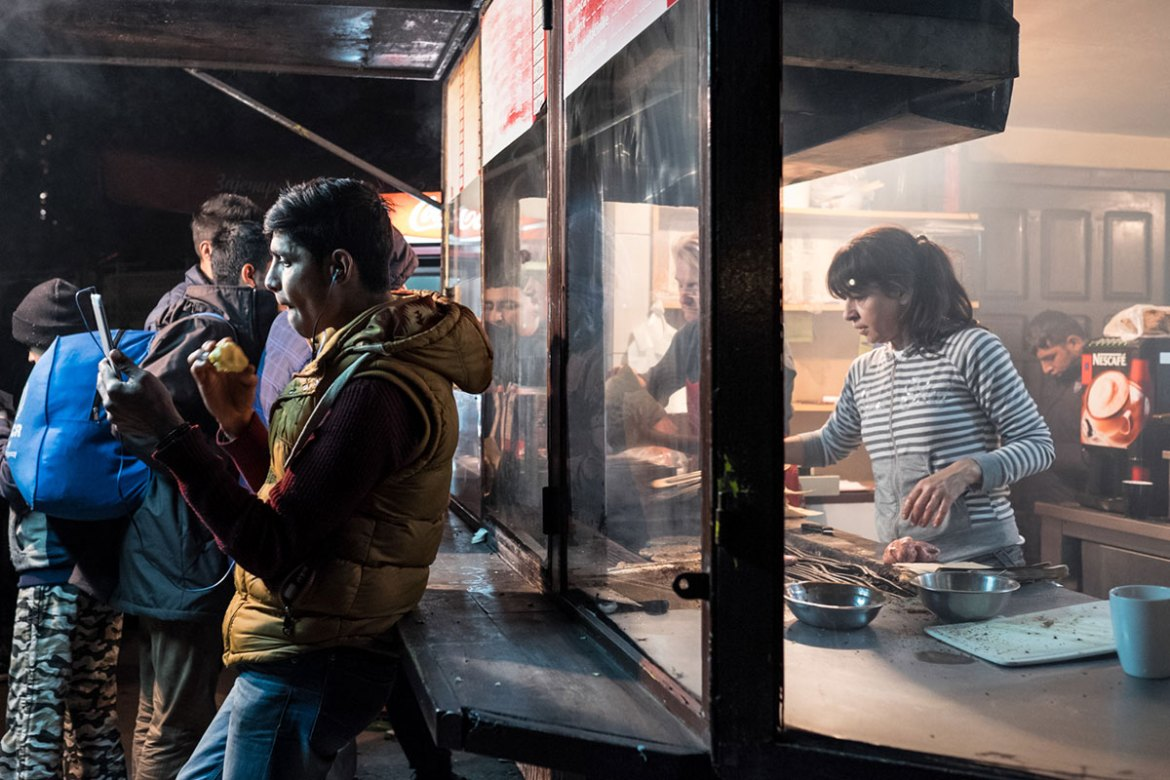 Refugees buy food at a kiosk in the park located next to Belgrade's central train and bus station. The place has come to be known as 'Afghan Park'. [Ioana Moldovan/Al Jazeera]