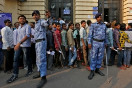 Riot police control people queuing to exchange old high denomination bank notes at a bank in New Delhi [Reuters]