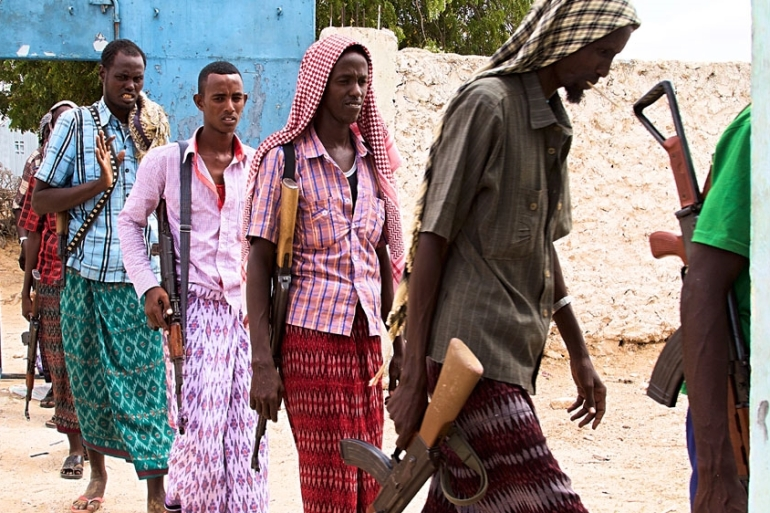 Former government fighters line up in preparation for negotiations between al-Shabab leaders and town elders to determine their fate [Hamza Mohamed/Al Jazeera]