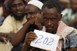 An Ethiopian refugee holds his travelling number as he waits to be evacuated from western Yemen [Hani Mohammed/AP]