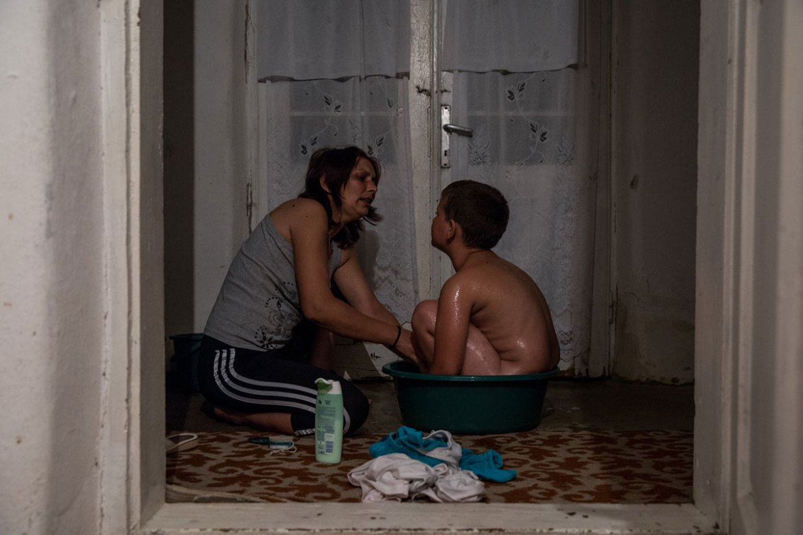 Carmen, 39, bathes her son, Rares, 9, before going to bed. She has been a nurse in Gangiova commune for 14 years. In this commune there is no running water system in place, and people are still using water wells. [Ioana Moldovan/Al Jazeera]