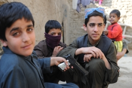 Boys from Kunduz play with a toy gun at an IDP camp outside Kabul - they're among the 1.2 million displaced in the country [Al Jazeera]