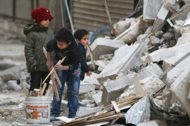 Children collect firewood amid debris in rebel-held al-Shaar neighbourhood in Aleppo [File: Abdalrhman Ismail/Reuters]