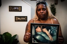 Sandra Harris holds a picture of her son, Eric, who was killed by police earlier this year [Patrick Strickland/Al Jazeera]