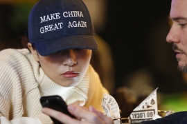 A woman wears a cap with a China message that is reminiscent of Trump's campaign slogan 'Make America Great Again' at a bar in Beijing [EPA]
