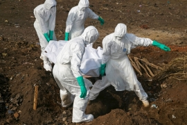 Health workers carry the body of a suspected Ebola victim for burial at a cemetery in Freetown, Sierra Leone, December 21, 2014 [Baz Ratner/Reuters]