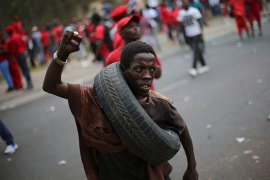 A member of the Economic Freedom Fighters party carries a tyre around his neck as protesters call for the removal of President Jacob Zuma in Pretoria, South Africa. [Siphiwe Sibeko/Reuters]