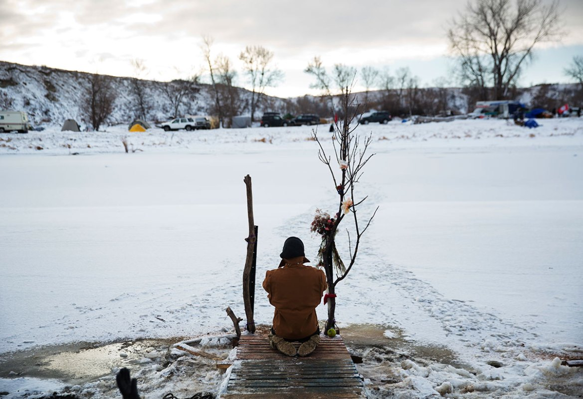 Army veteran Nick Biernacki, of Indiana, prays at the Cannonball River in the Oceti Sakowin camp. Tribal elders asked the military veterans joining the large Dakota Access pipeline protest encampment not to confront law enforcement officials. [David Goldman/AP]
