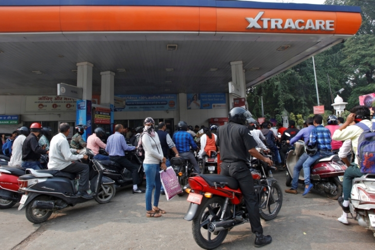 People wait for their turn to fill fuel at a petrol pump in the city of Lucknow [File:Pawan Kumar/Reuters]