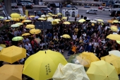 Pro-democracy protesters carrying yellow umbrellas, symbol of the Occupy Movement, mark the second anniversary of the movement outside government headquarters in Hong Kong [Reuters]