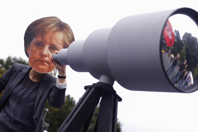 A woman wearing a mask depicting Chancellor Angela Merkel behind a mock telescope during a protest calling for the protection of digital data privacy in Berlin [Thomas Peter/Reuters]