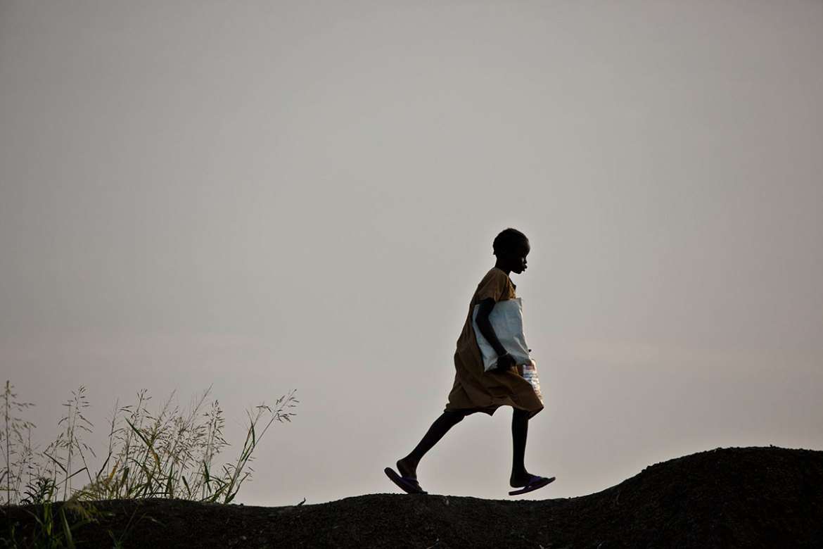 A young girl runs to school along a ridge in the Benitu camp. Nearly two million children are missing out of school. [Kate Holt/UNICEF]