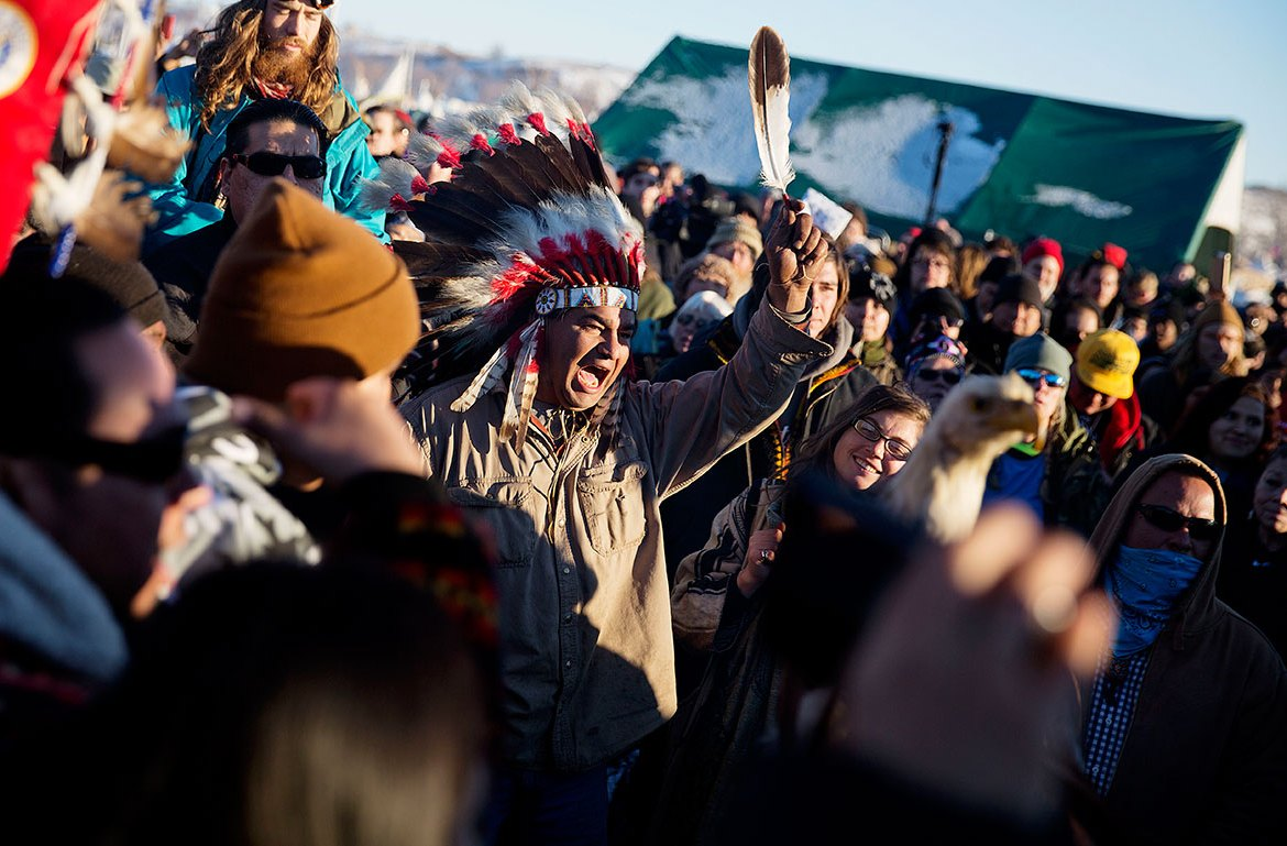 A crowd gathers in celebration at the Oceti Sakowin camp after it was announced that the US Army Corps of Engineers won't grant easement for the Dakota Access oil pipeline in Cannon Ball, North Dakota. [David Goldman/AP]