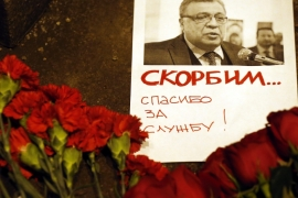 Flowers lie near a picture of Russia's ambassador to Turkey Andrey Karlov, outside the Russian foreign ministry in Moscow on December 19 [EPA]