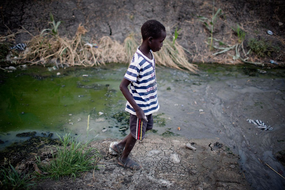 A boy walks by a dirty stream. In 2016 Unicef reunited 4,500 children with their families. UNICEF is supporting children in the camp providing services ranging from education to nutrition, in partnership with other international organisations. [Kate Holt/UNICEF]