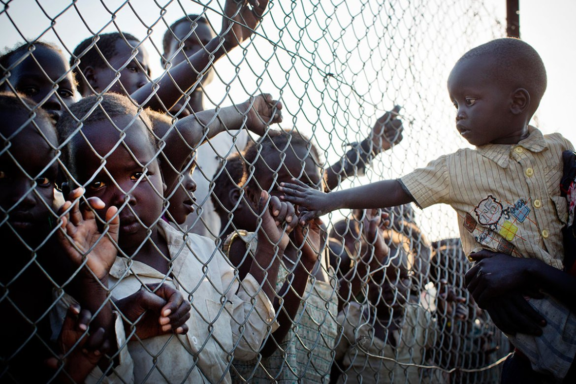 A baby reaches out to touch children through a fence that divides the Malkal camp into different parts. The fence separates two ethnic groups. More than 33,000 people from the Nuer and Shiluk tribes are now living in the camp. [Kate Holt/UNICEF]