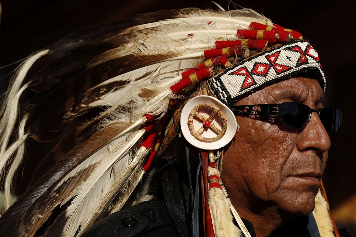 Chief Arvol Looking Horse of Green Grass South Dakota, the spiritual leader of the Lakota, Dakota and Nakota Sioux Nations, listens to speakers inside the Oceti Sakowin camp near the Standing Rock Indian Reservation. [Lucas Jackson/Reuters]